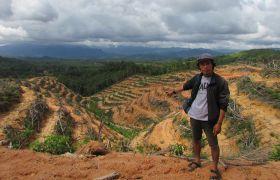 Dossier_Wahli-MItarbeitender zeigt auf neuen Palmölplantage